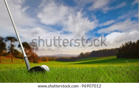 hitting golf ball towards green on fairway - stock photo