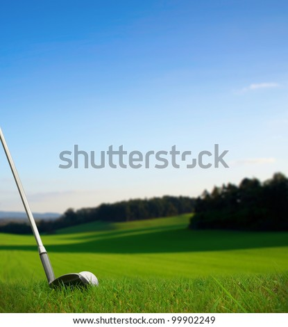 hitting golf ball with club along fairway towards green - stock photo