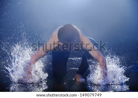 Hitting the water. Young male dancer in black fedora dancing on the wet floor