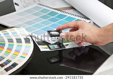 Hnad man with black glass standing on a leaf of the test print and pantone - stock photo