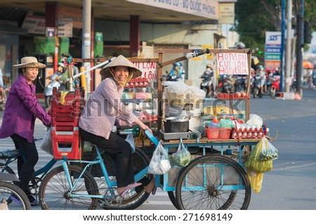 HO CHI MINH - APRIL 19, 2015: Two unidentified local women cooks drive their bicycle carts along Truong Chinh Street to their point of work. Their business is cooking food in the street. - stock photo