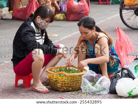 Ho Chi Minh City-Nov 1st 2013: Street vendors sorting vegetables Vendors can be found all over the city. - stock photo