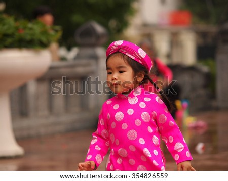 HO CHI MINH CITY, VIET NAM- FEB16:,Portrait of a  Asian  girl on traditional festival costume. Cute little Vietnamese girl  in ao dai dress smiling. Tet holiday. Lunar New Year Vietnam, Feb 16, 2015 - stock photo