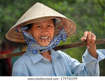 HO CHI MINH CITY, VIETNAM - APRIL 15, 2009: A woman in a traditional Vietnamese hat takes a break from selling fruit and vegetables from her baskets in the streets of Saigon. - stock photo