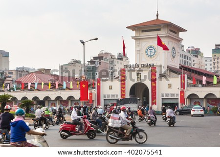 HO CHI MINH CITY, VIETNAM - FEBRUARY 2 2016: Cars and motorcycles rush around the Saigon Central Market known locally as Ben Thanh. - stock photo