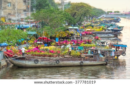 Ho Chi Minh City, Vietnam - February 6th, 2016: boating along canal carry flowers with apricot, confetti, almond tree to sell everyone distillation welcome spring Tet in Ho Chi Minh City, Vietnam - stock photo