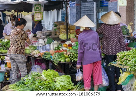 HO CHI MINH CITY, VIETNAM - MAR 1: Unidentified women buys and sells vegetable at the market on the street of Ho Chi Minh City on Mar 1, 2014 - stock photo