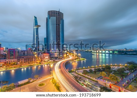 HO CHI MINH CITY, VIETNAM - MAY 18: City and traffic light trails after rain with the modern building at background in Ho Chi Minh City on May 18, 2014 - stock photo