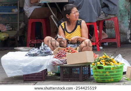 Ho Chi Minh City, Vietnam-Nov 1st 2013: Street vendor selling fruit. Street vendors are everywhere in the city - stock photo