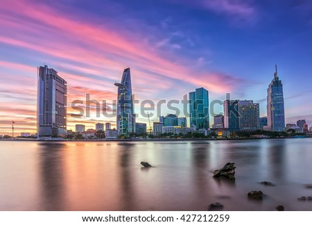 Ho Chi Minh City, Vietnam - November 20th, 2015: Sunset riverside purple clouds sky at the end of day along beautiful sparkling skyscrapers coal brighter show development in Ho Chi Minh City, Vietnam - stock photo