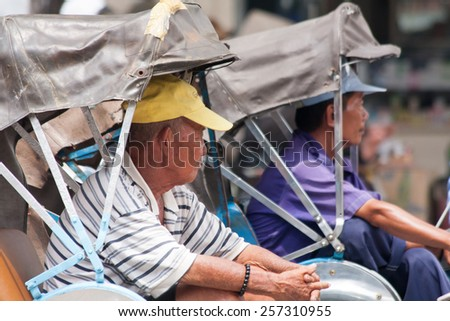 Ho Chi Minh City, Vietnam-October 30th 2013: Rickshaw drivers waiting for fares. Rickshaws are dying out as more people obtain their own transport. - stock photo