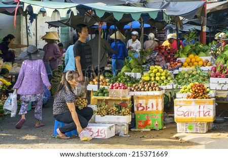 HO CHI MINH CITY, VIETNAM - SEPTEMBER 05: An unidentified Vietnamese woman is smiling in her's fruit shop in the market in Hochiminh city, Vietnam on Sep 05, 2014.  - stock photo