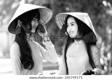 Ho Chi Minh City, Vietnam - September 13rd, 2015: A girl student was watching her friend with a smile and beautiful bright eyes showing innocent beauty of students in Vietnam