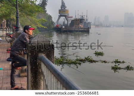 Ho Chi Minh City, Vietnam-29th Oct 2013: Man fishing in the Saigon river. The river rises in Cambodia and flows for 230 kms before empting into the Nha Be river. - stock photo
