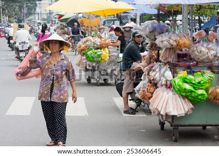 Ho Chi Minh City, Vietnam-30th Oct 2013: Woman carrying shopping and street vendors on market in Cholon. Cholon is the Chinatown area of the city. - stock photo