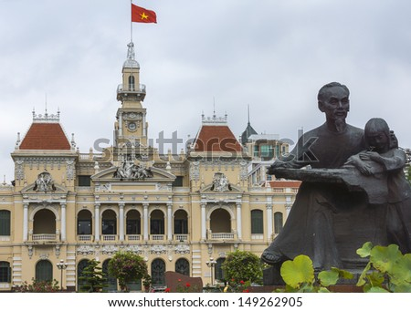 Ho Chi Minh statue and Saigon City Hall with flag. Combination shot of the statue with the chateau-like French-built city hall, the center of power in Ho Chi Minh City. - stock photo