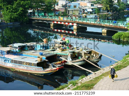 HO CHI MINH, VIETNAM- AUG 18: Scene on river, wooden boat of merchant anchor at polluted canal, bridge and boat reflect on water, residential along ditch, woman walk on street, Vietnam, Aug 18, 2014 - stock photo