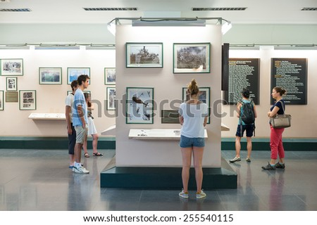 HO CHI MINH, VIETNAM - AUGUST 12, 2014: Unidentified tourists watch photographs at the War Remnants Museum. It primarily contains exhibits relating to the American phase of the Vietnam War. - stock photo