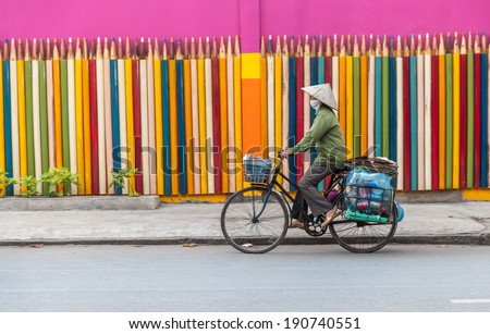 HO CHI MINH, VIETNAM - DEC 29: An unidentified street vendor with conical hat on street across a colorful pencil background, Ho Chi Minh City (Saigon), Vietnam on December 29, 2013.  - stock photo