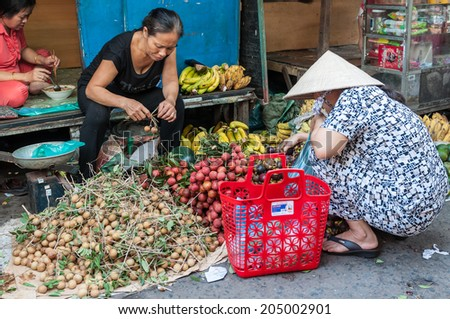 HO CHI MINH, VIETNAM - JULY 13: Unidentified woman trades fresh and organic fruits at Ngo Gia Tu market on July 13, 2014 in Ho Chi Minh city, Vietnam. - stock photo