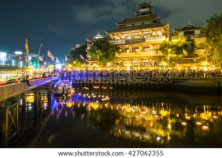 Ho Chi Minh, Vietnam - May 20, 2016: Beautiful flower garlands and colored lanterns are released for celebrating Buddha's birthday in Saigon River by night, a Eastern culture. - stock photo