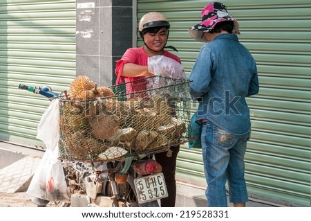 HO CHI MINH, VIETNAM - SEP 23: Unidentified women street vendor selling durian at street market on September 23, 2014 in Ho Chi Minh city, Vietnam. - stock photo