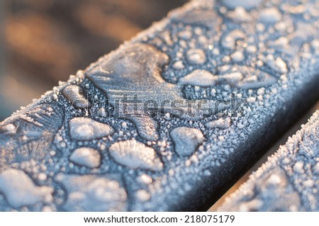 Hoarfrost covered wooden bench. Close up. - stock photo