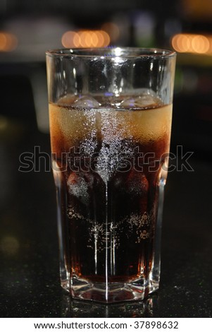 Hoarfrosted glass with cola and ice on a bar rack