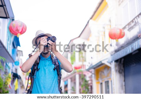 Hobby and travel. Young man with backpack taking photo with his camera on asian street. - stock photo