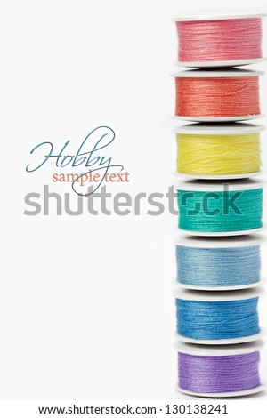 Hobby concept: colorful bobbins with cotton thread on white background with sample text - stock photo
