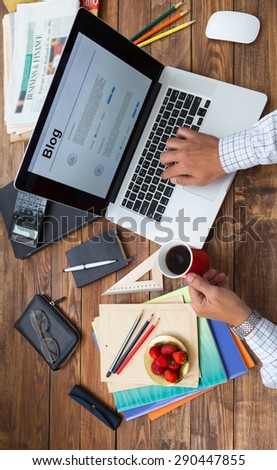 Hobby time concept vertical. Man working computer handcrafted rough wooden desk overhead top view keeping coffee mug many office supplies in creative disorder focus on plate with fresh strawberry food - stock photo