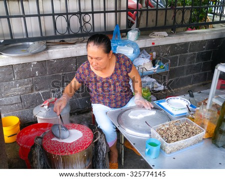 Hochiminh City, Vietnam - On October 3, 2015: the woman with the her daughter doing dishes rolls for sale. Roll cake is a traditional rustic dishes from Vietnam