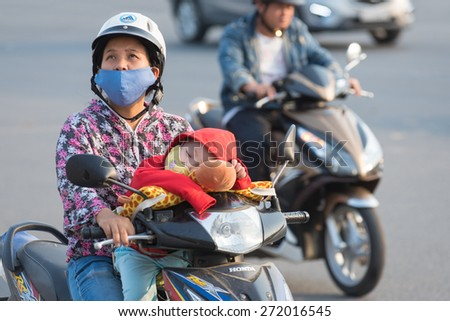 HOCHIMINH, VIETNAM - APRIL 19, 2015: An unidentified motorcyclist and sleeping son wait at red traffic lights in Truong Chinh Street during rush hours. The main transport in Vietnam is motorcycle. - stock photo