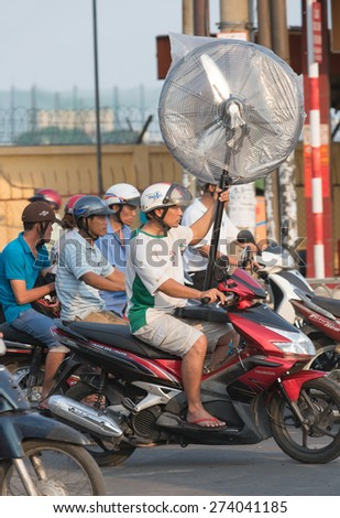 HOCHIMINH, VIETNAM - APRIL 19, 2015: An unidentified motorcyclist drives an electric fan in Truong Chinh Street during rush hours. The main means of cargo transportation in Vietnam is motorcycle. - stock photo