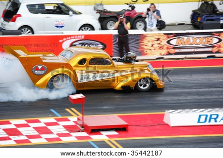 HOCKENHEIM, GERMANY - AUGUST 16 : Driver Rolf Ammann performs a burnout during qualifying at nitrolympics drag racing event August 14-16, 2009 at Hockenheimring, Hockenheim, Germany. - stock photo