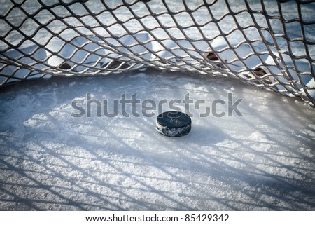 Hockey net with puck in goal - stock photo