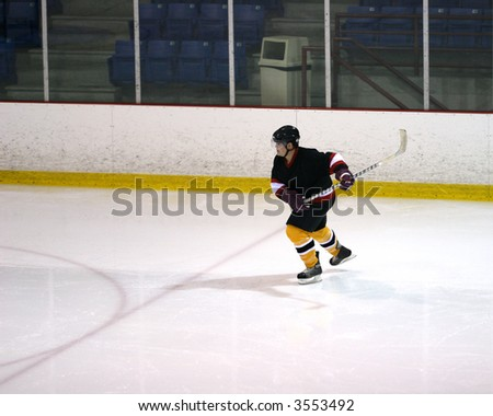 Hockey player in black skating away from the boards.