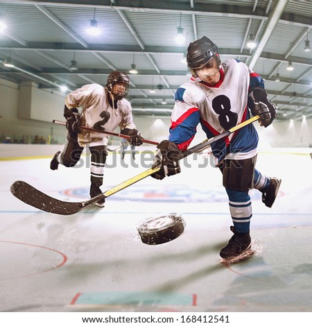 Hockey player shoots the puck and attacks - stock photo