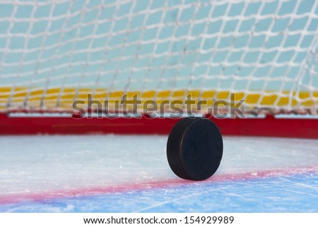 Hockey puck stand on side in front of goal net. Close view - stock photo