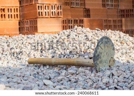 Hoe for construction process on a heap of stone at construction site  - stock photo