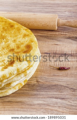 Hogh angle shot of a baked pastry dish, hot pepper and a rolling pin placed on a wooden talbe - stock photo
