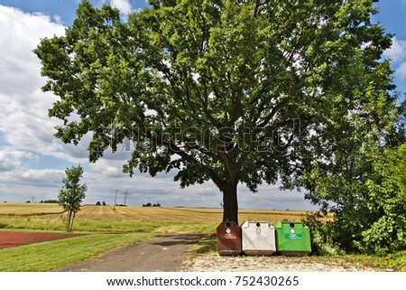 HOHEBUCH, GERMANY July 15, 2016 - 3 Recycling containers are standing under a tree in front of a rural southern German landscape.