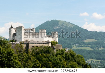 Hohensalzburg Castle atop the Festungsberg with the Gaisberg mountain beyond on a summer day in Salzburg, Austria - stock photo