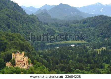 Hohenschwangau Castle in Bavaria, with surrounding woods. Mountains and a lake in the background. - stock photo