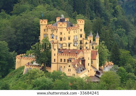Hohenschwangau Castle in Bavaria, with surrounding woods. Yellow walls, roofs and battlements covered with red tiles. - stock photo