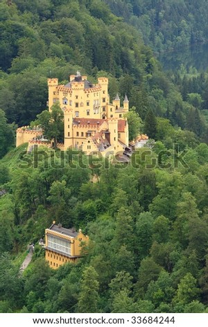 Hohenschwangau Castle in Bavaria, with surrounding woods. Yellow walls, roots and battlements covered with red tiles. - stock photo