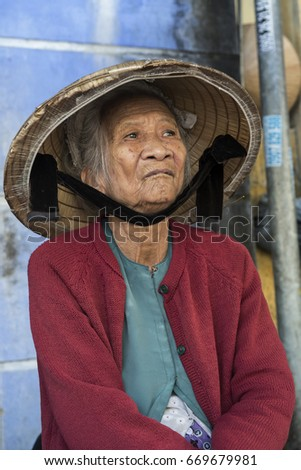 HOI AN, VIETNAM – DECEMBER 2012: Old Vietnamese woman with the traditional conical hat.
