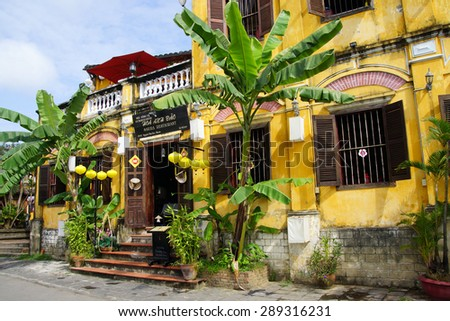 HOI AN, VIETNAM - FEB 3, 2015 - Traditional yellow ochre building with palm trees, Hoi An, Vietnam - stock photo