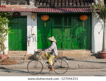 HOI AN, VIETNAM - JANUARY 10: An unidentified woman rides her bicycle on January 10, 2008 in Hoi An, Vietnam. Hoi An, a UNESCO World Heritage site, is a major touristic destination in Central Vietnam.