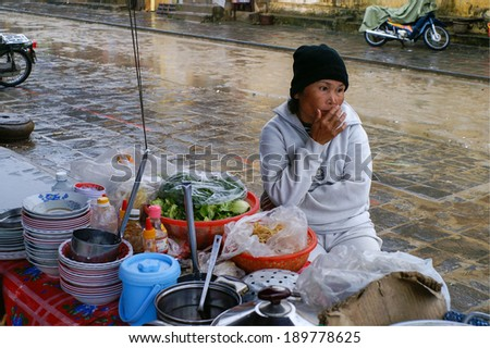 Hoi-An, Vietnam - January 24th, 2008: vietnamese soup-seller sits at her street-booth and looks thoughtfully into the rain
